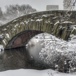 A photo of a stone bridge in Central Park with Falling Snow.